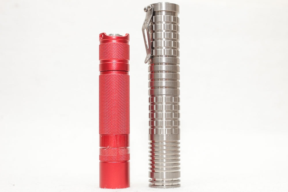 18650 style Reylight titanium flashlight next to convoy s2+