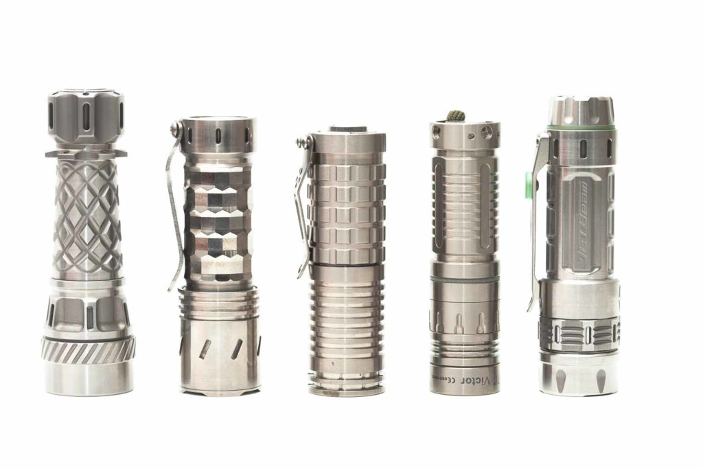 5 titanium EDC flashlights next to eachother
